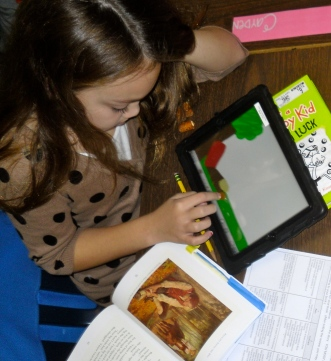 Natalie with all of her resources: novel, rubric, iPad